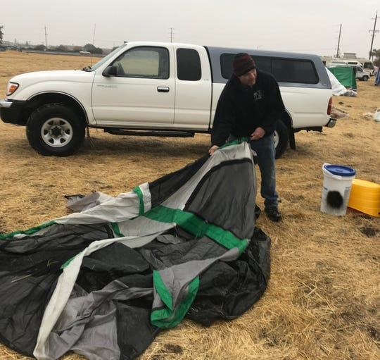 James Dollaz of Magalia breaks down his tent Wednesday at the tent city outside the Chico Walmart as he prepares to seek refuge at an evacuation shelter in Gridley