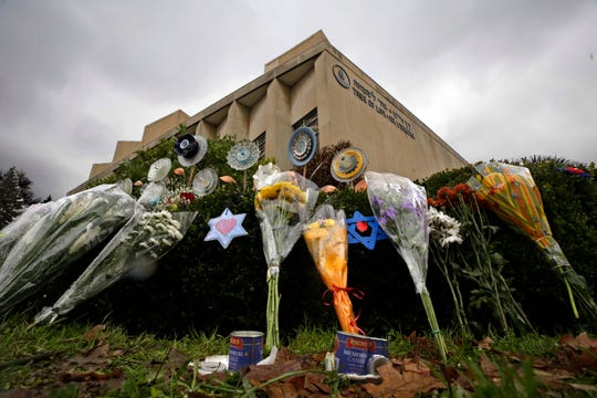 In this Tuesday, Nov. 20, 2018 photo, a makeshift memorial of flowers rests on bushes outside the Tree of Life Synagogue in Pittsburgh. Mass shootings, hurricanes, fires - for many people across the nation, 2018 was a year of loss unlike any other. As the quintessentially American holiday of Thanksgiving approaches, some will abandon traditions or chose not to mark the holiday at all. Others will celebrate new friendships forged in the wake of tragedy.