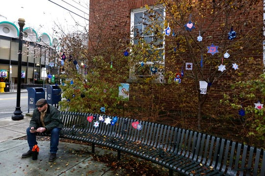 "In this Tuesday, Nov. 20, 2018 photo, crocheted or knitted Stars of David hang from bushes outside the post office in the Squirrel Hill neighborhood of Pittsburgh. They are part of a Facebook group-initiated project, Jewish Hearts for Pittsburgh. A sign thanks people for participating in ""an act of Tikum Olam (the Jewish concept of repairing the world) by bring visual symbols of love to the Pittsburgh community and honoring the memories f the victims of the Tree of Life synagogue shooting."