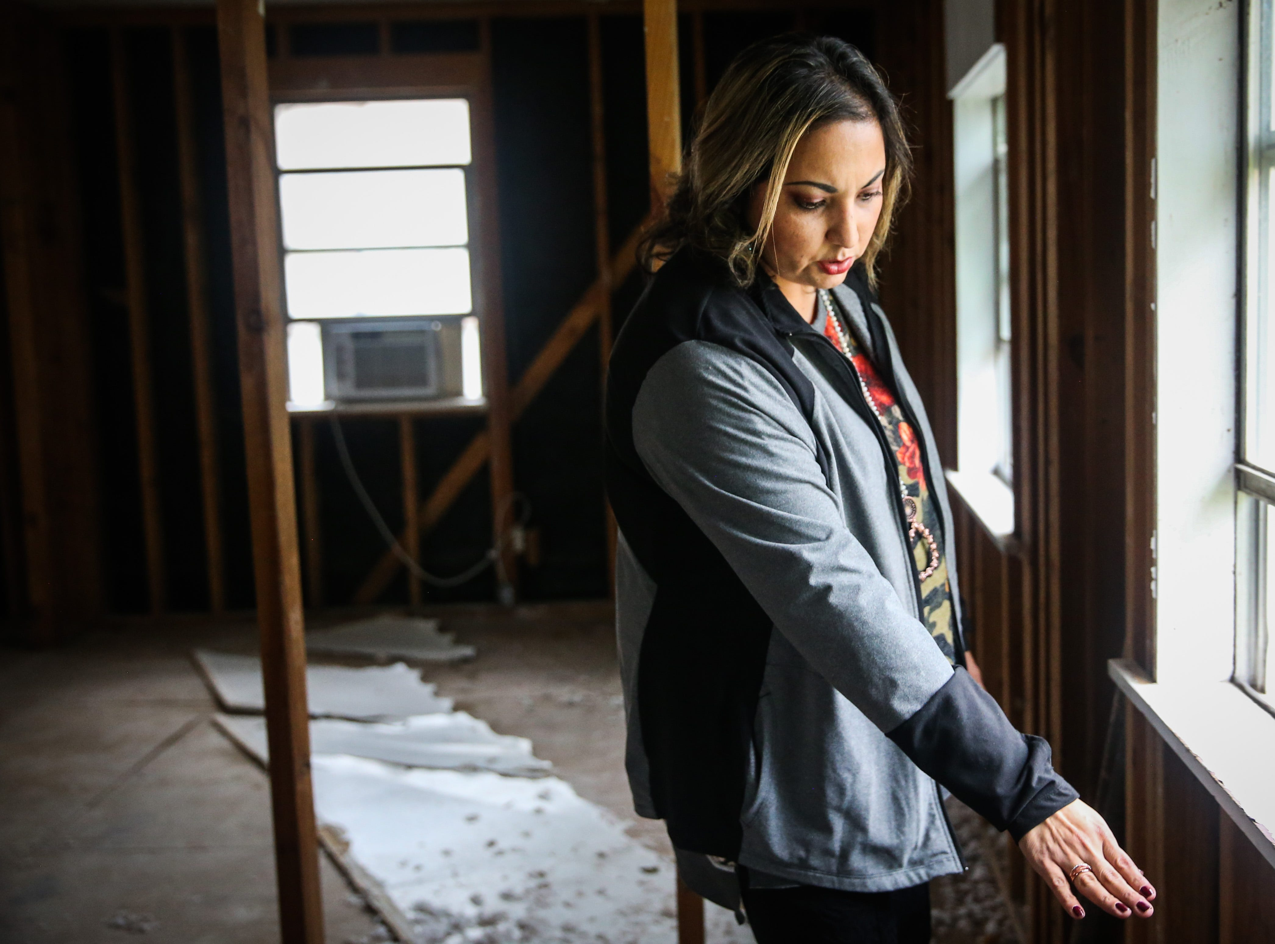 Crystal Villanueva points out where the water reached Nov. 8, 2018, during the Sept. 21 flood in Sonora.