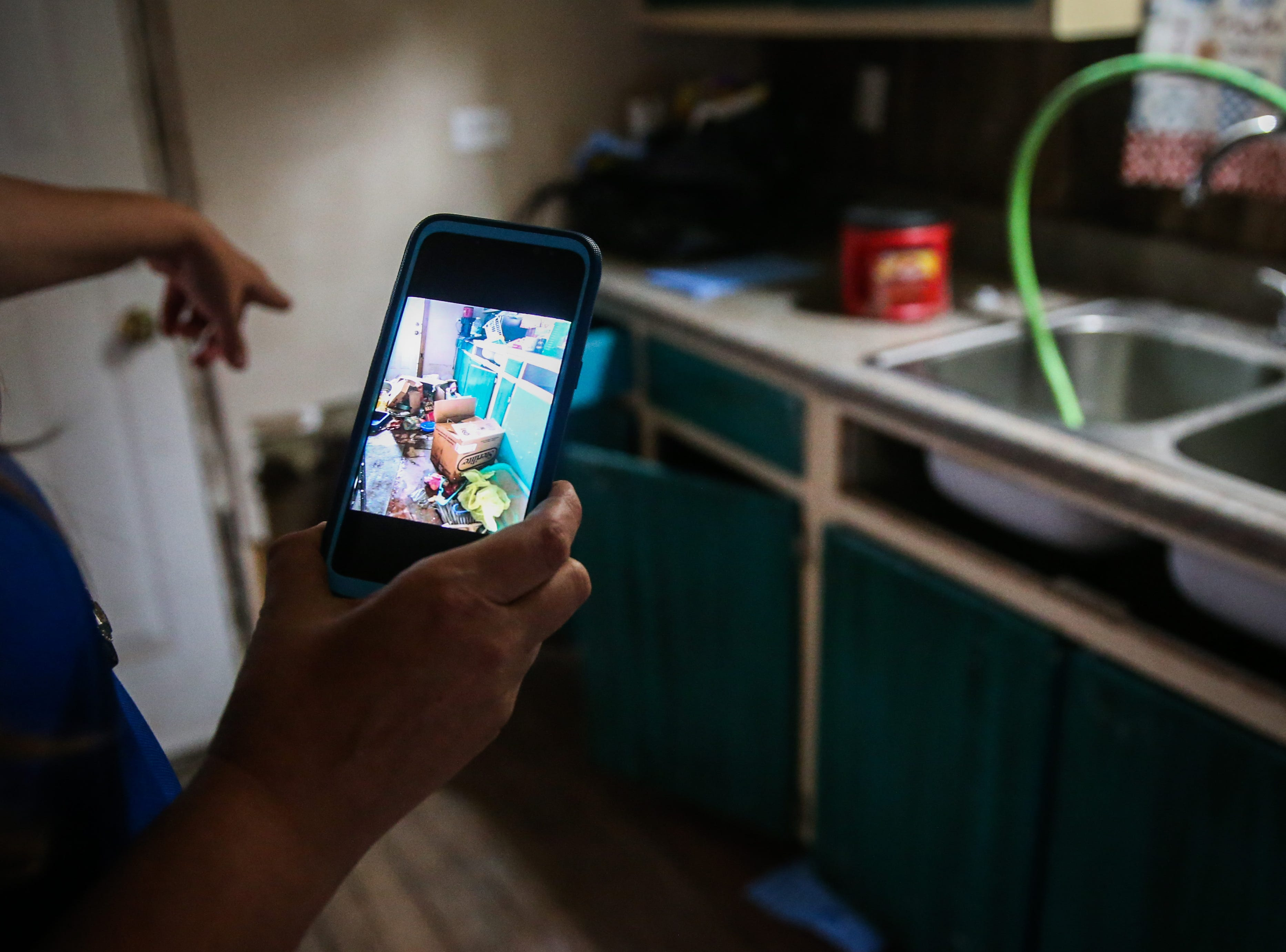 Sarah Webb holds up a photo of flooded boxes on her phone and points to the spot in her kitchen Nov. 8, 2018, after the Sept. 21 flood in Sonora.