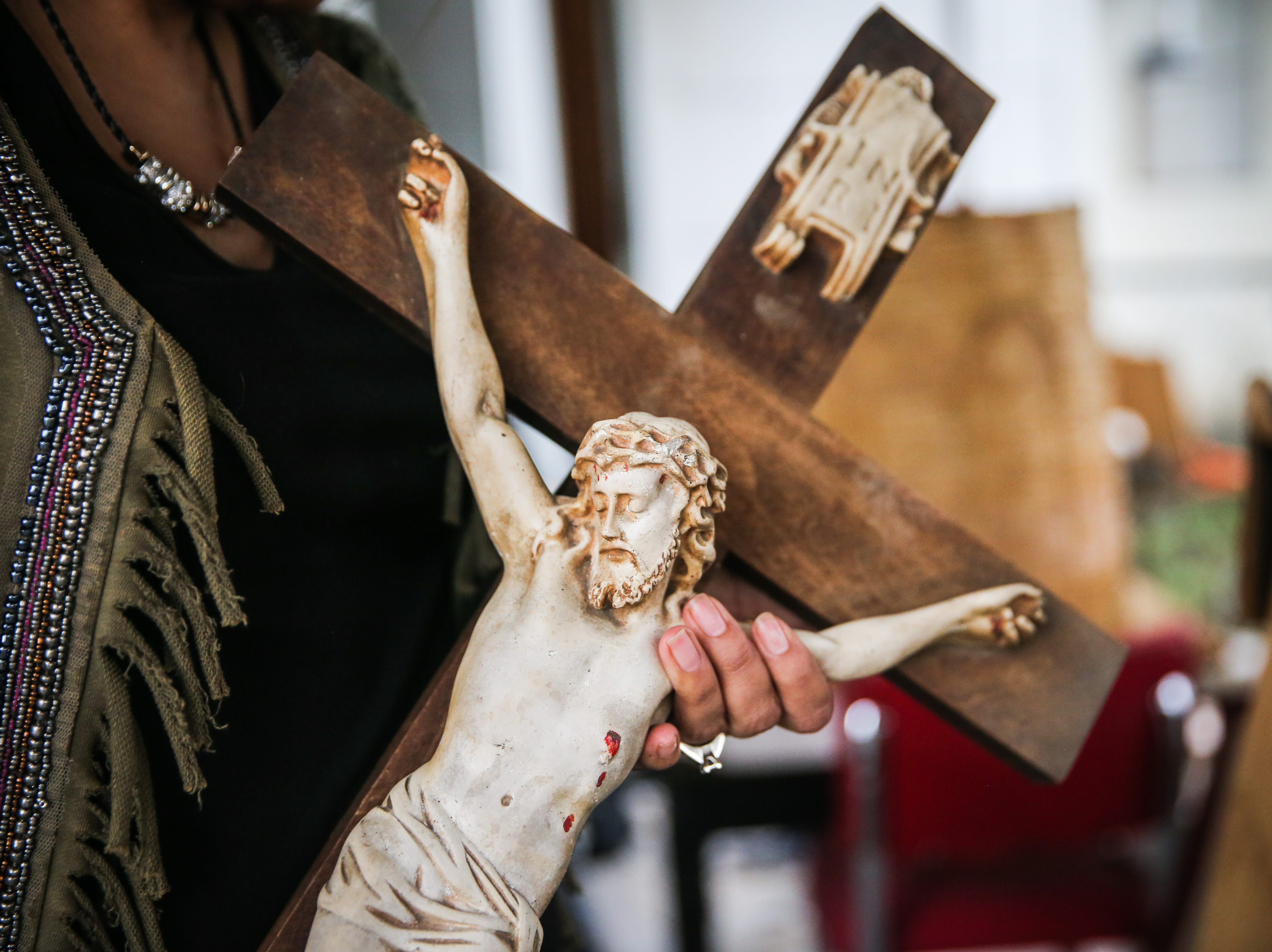 Belia Fay holds a cross she salvaged Nov. 8, 2018, from the Sept. 21 flood in Sonora.