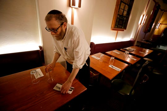 In this Tuesday, Nov. 20, 2018 photo, Daniel Cohen owner of Pinskers Books and Judaica, and the adjoining cafe, sets a table for the dinner service in the Squirrel Hill neighborhood of Pittsburgh.