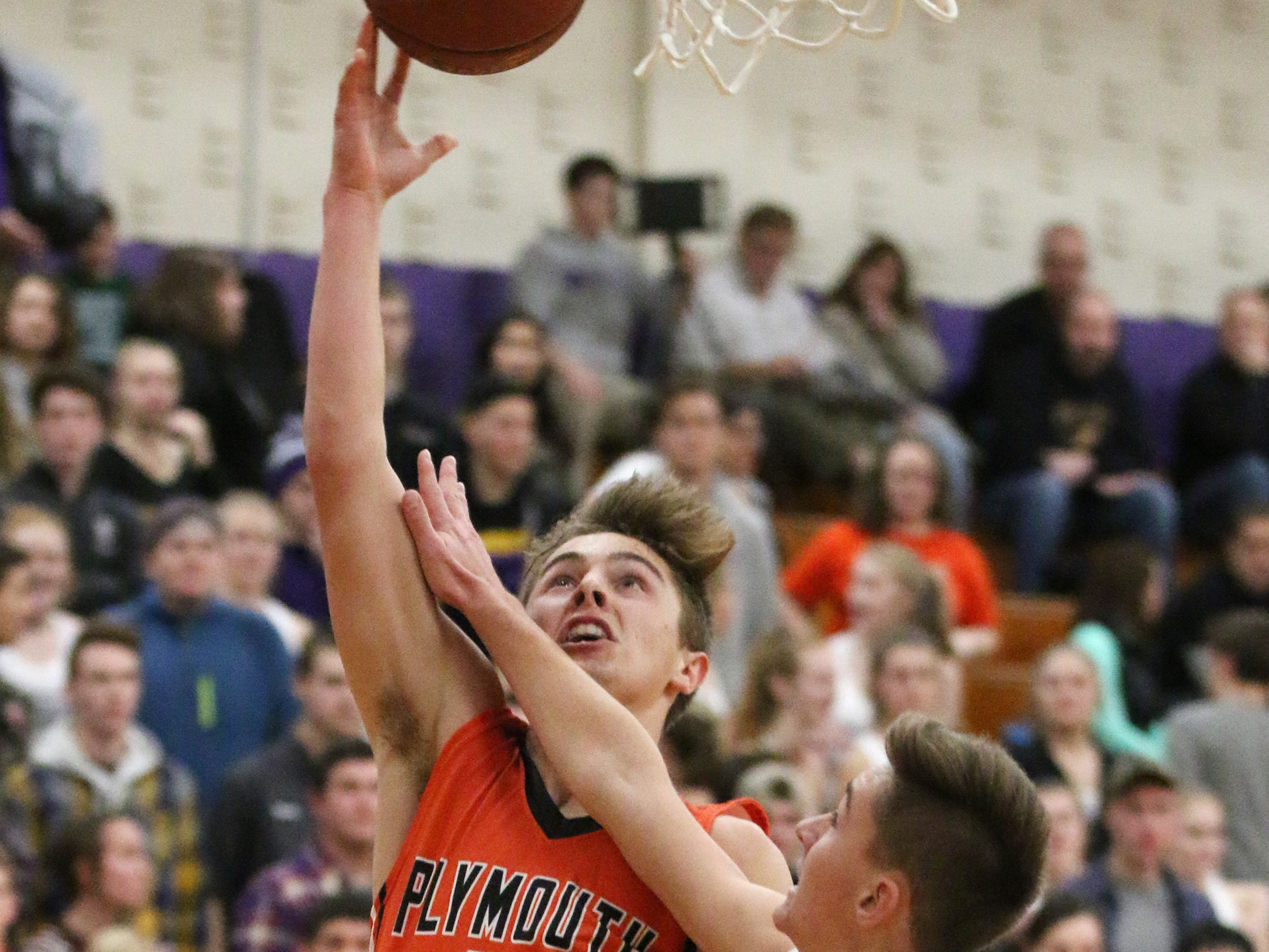 Plymouth's Cole Booth (11) drives to the basket by a Sheboygan Falls player, Tuesday, November 20, 2018, in Sheboygan Falls, Wis.