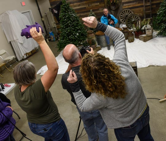 Photographers join forces to draw the attention of a pet during the Tri-County Humane Society's Santa Paws fundraiser Friday, Nov. 16, in St. Cloud.