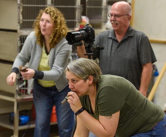Brooke Strassburg uses a duck call to get a pet's attention as Steve Huss and Wendy Curry also try for the best expression during the Tri-County Humane Society's Santa Paws fundraiser Friday, Nov. 16, in St. Cloud.