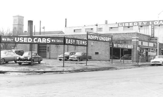 The DeSoto car dealership is shown circa the 1930s on the corner of Minnesota Highway 23 and Seventh Avenue South. The site is now a dry cleaning business.
