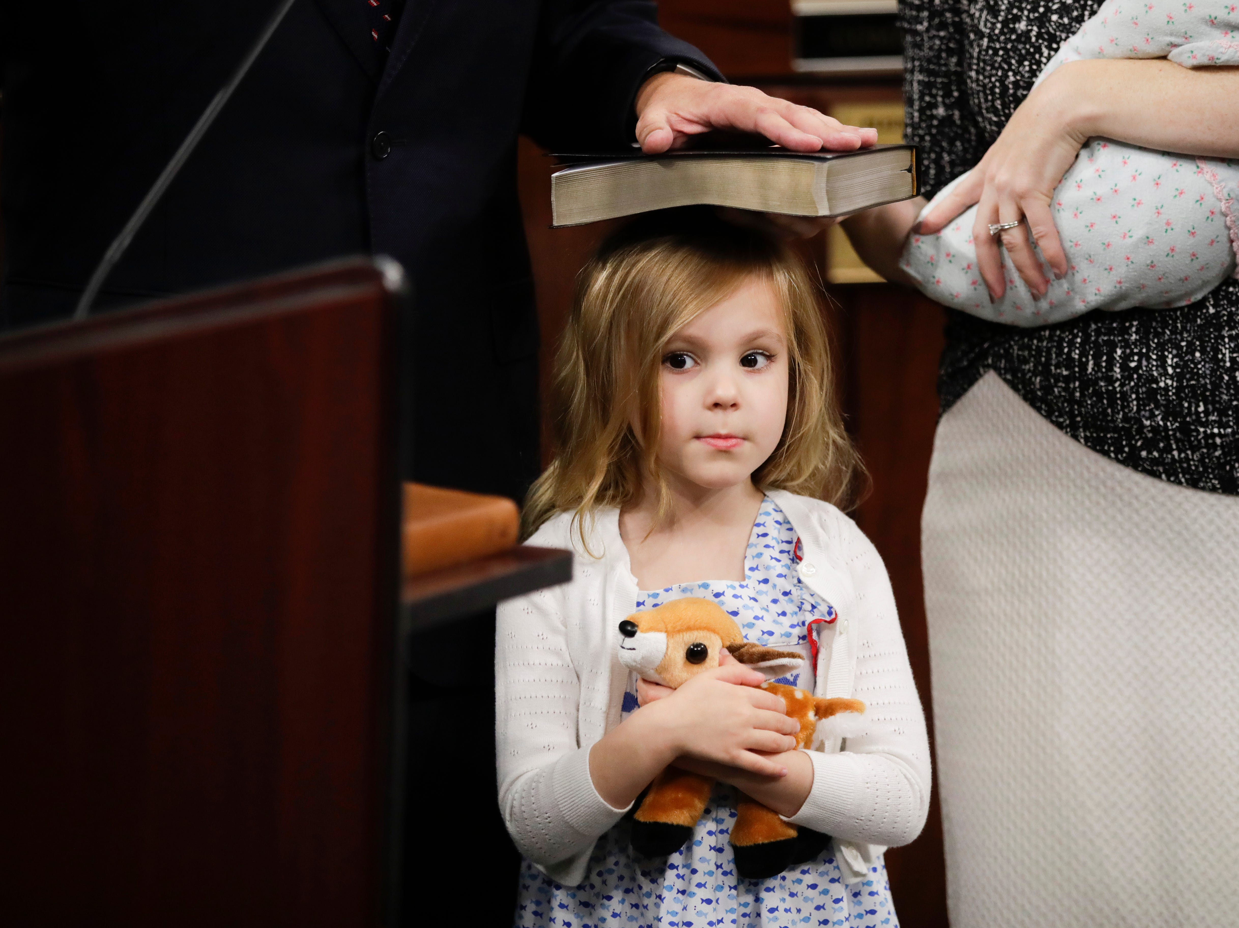 Madeline Minor, 4, holds up the Bible with her head as her father, newly elected County Commissioner Rick Minor is sworn in during the County Commission reorganization and installation meeting Tuesday, Nov. 20, 2018.