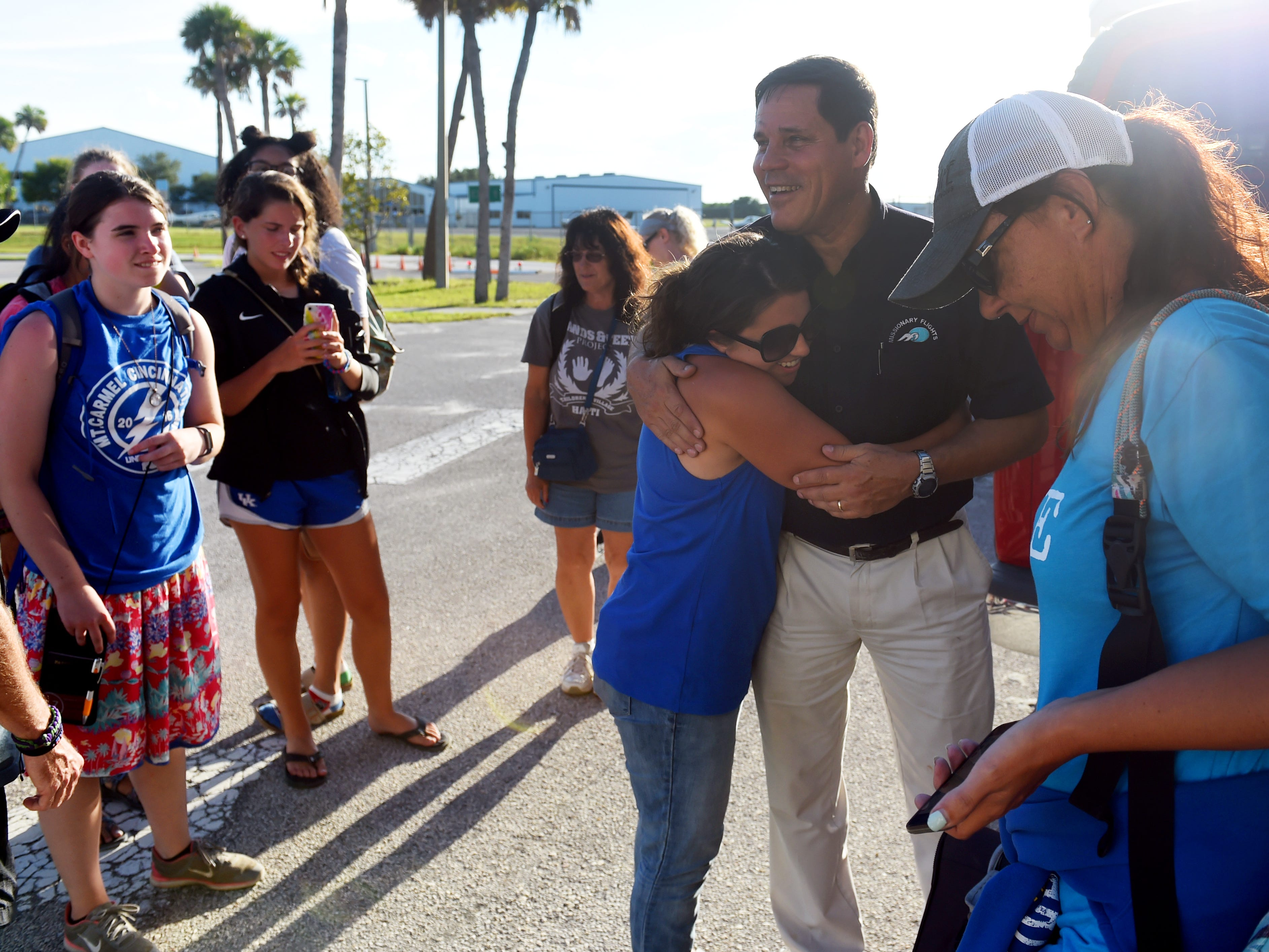 """Joe Karabensh, president of Missionary Flights International, receives a hug from Kinsley Smith, of Agape to the Nations, on Tuesday, July 10, 2018 after Smith and 22 fellow missionaries land safely at Treasure Coast International Airport and Business Park in Fort Pierce. Smith and her group were serving on a mission trip in Haiti when riots broke out ending their trip early. Due to roads blocks and civil unrest, the group was unable to reach the main airport to evacuate, when they were able to coordinate with Missionary Flights International to get out of the country. """"By God's beautiful, just how he aligns everything, we were able to use Missionary Flights International to get this team out today,"""" Smith said. """"It truly has been a relief and a breath of fresh air that we can step on U.S. soil today. But, we do miss our friends in Haiti and we are praying for them for peace because they are our family and friends there too."""""""