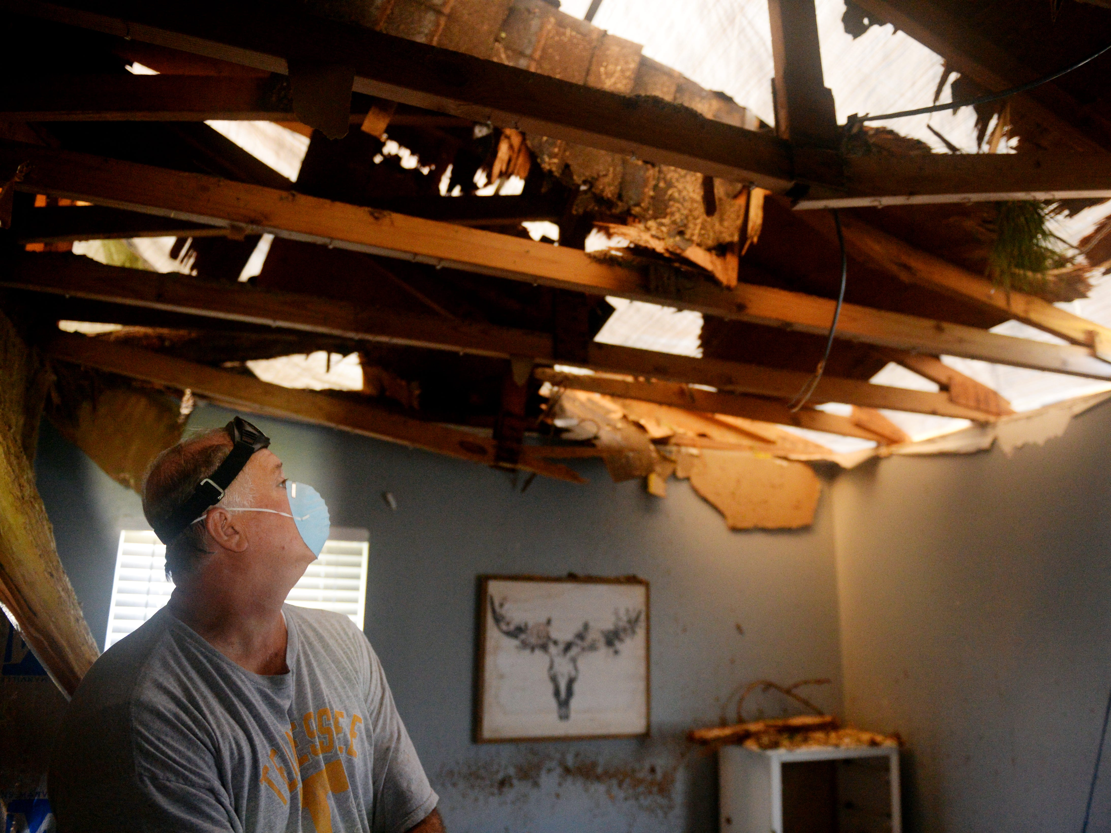 Oct. 14, 2018, Panama City, FL, USA; Allen Wykle surveys the damage done to his cousin's home after a tree fell on the roof and came through the ceiling from Hurricane Michael. Wykle's cousin, Micaela Johnson and her husband  Josh, were out of town during the storm. The home is property owned by Fellowship Baptist Church where Josh Johnson is an associate paster.