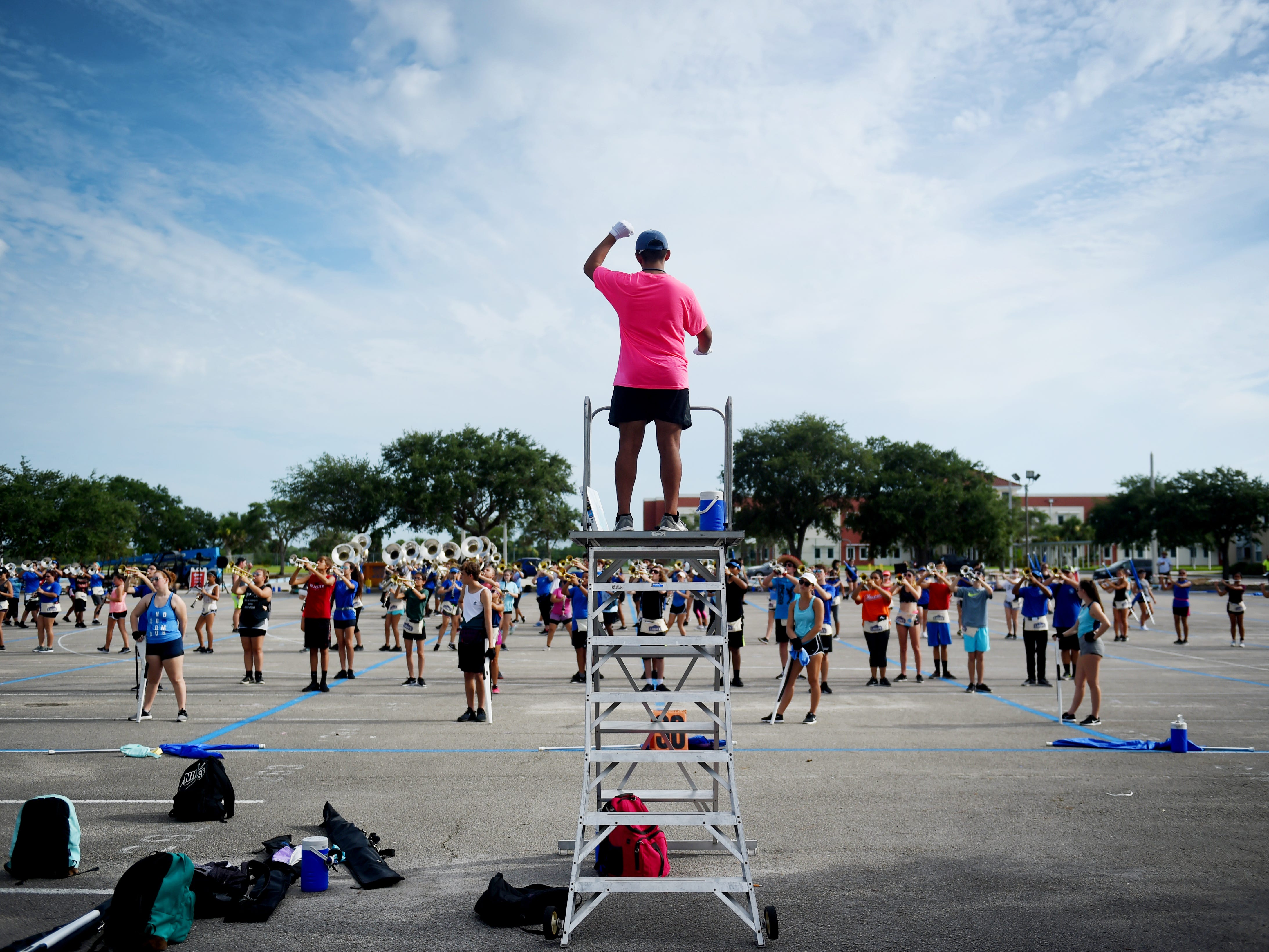 """Sebastian River High School marching band senior drum major Eduardo Ambris helps lead fellow band members through music and marching drill Tuesday, July 31, 2018 during the second week of band camp at the school. """"The Sebastian River High School Band, since its inception 25 years ago, our motto has been  'Strive for the highest' so our show is kind of a play on that motto,"""" said Ashby Goldstein, Sebastian River High School band director. """"Our show is called 'To the Highest' so it's all about things reaching upward."""" Sebastian River High School, as well as the band, will be celebrating it's 25th anniversary this year. """"We'll be looking back at the last 25 years and paying homage to everything that we've done,"""" Goldstein said. The 2018 marching band consists of about 300 students and will have the honor of marching in the New York City St. Patrick's Day Parade in March 2019."""