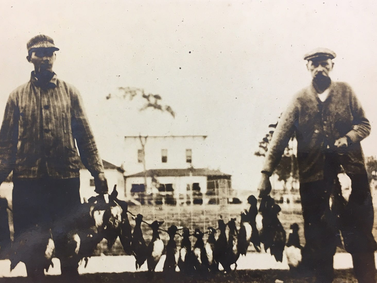 Two men holding a sting of ducks from the Two Hours Duck Hunt along the Indian River, pre-1920.