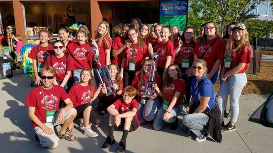Choral Director Ethan Kinkle poses with the Madrigal Singers after their first place win at Carowinds Park in Charlotte, N.C.