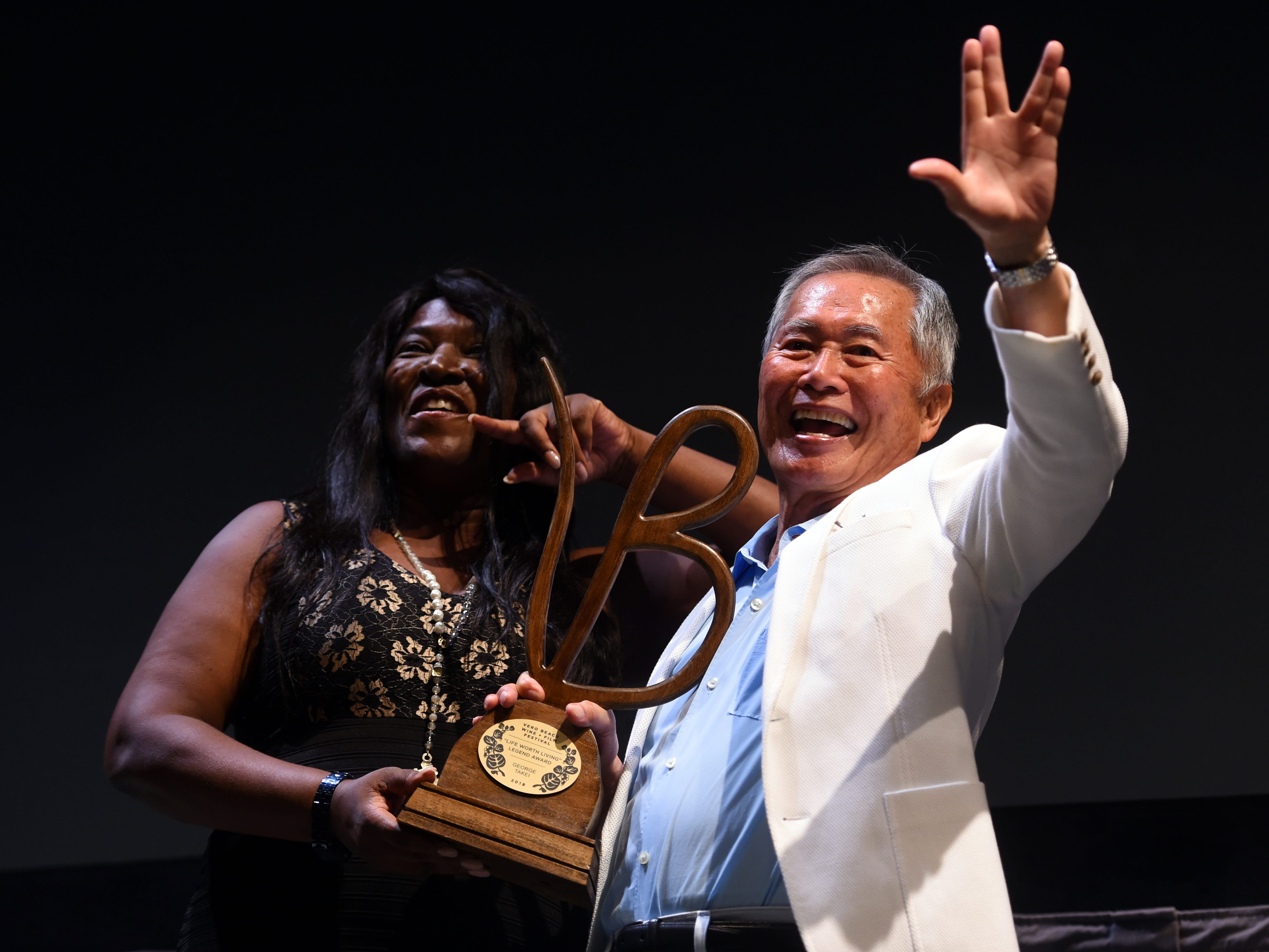 """Best known for his role of Sulu on the original Star Trek television series, stage and film actor George Takei waves to the crowd with a 'live long and prosper' sign on Friday, June 8, 2018 after receiving the Life Worth Living Legend Award from festival founder and executive director Jerusha Stewart at the 2018 Vero Beach Wine + Film Festival at the Riverside Theatre in Vero Beach. Takei spoke of his early years as a young actor, working with prominent film actors and his advocacy for the LGBTQ community. """"You got to have the strength, even after many rejections, to spring back and be able to approach that next interview with all the enthusiasm, the freshness and determination to do the best you can,"""" Takei said when asked what advice he would give to aspiring actors. """"Hang in there, be strong."""""""