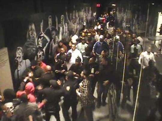 This April 21, 2018 still image from a surveillance video, provided by the U.S. Attorney's Office, Southern District of New York, shows the white flash of a gun being fired, lower left between two figures wearing red, at the Barclays Center in the Brooklyn borough of New York, where the rapper Tekashi 6ix9ine performed shortly afterward. The image was used by federal prosecutors to document alleged involvement by the rapper in several violent incidents to support their request to a judge that the rapper be denied bail. Prosecutors said this was a confrontation with a rival rapper's group; and someone in Hernandez's group fired the round in the air.