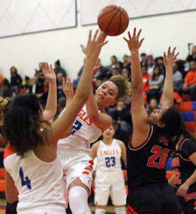 Sadi Clemons, center, of Canutillo leaps to pass the ball to a teammate under the basket during the Eagles' game with the El Paso High Tigers Tuesday night.