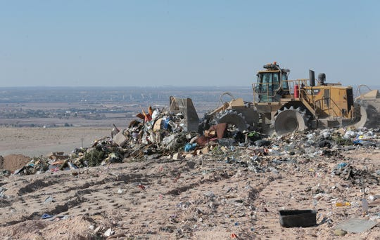 Heavy machinery compacts trash at the Greater El Paso Landfill just above the Clint valley, which can be seen in the background.