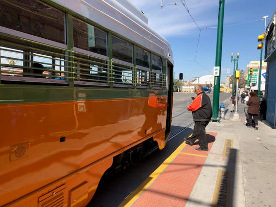 A passenger boards the El Paso Streetcar while taking video of his experience.