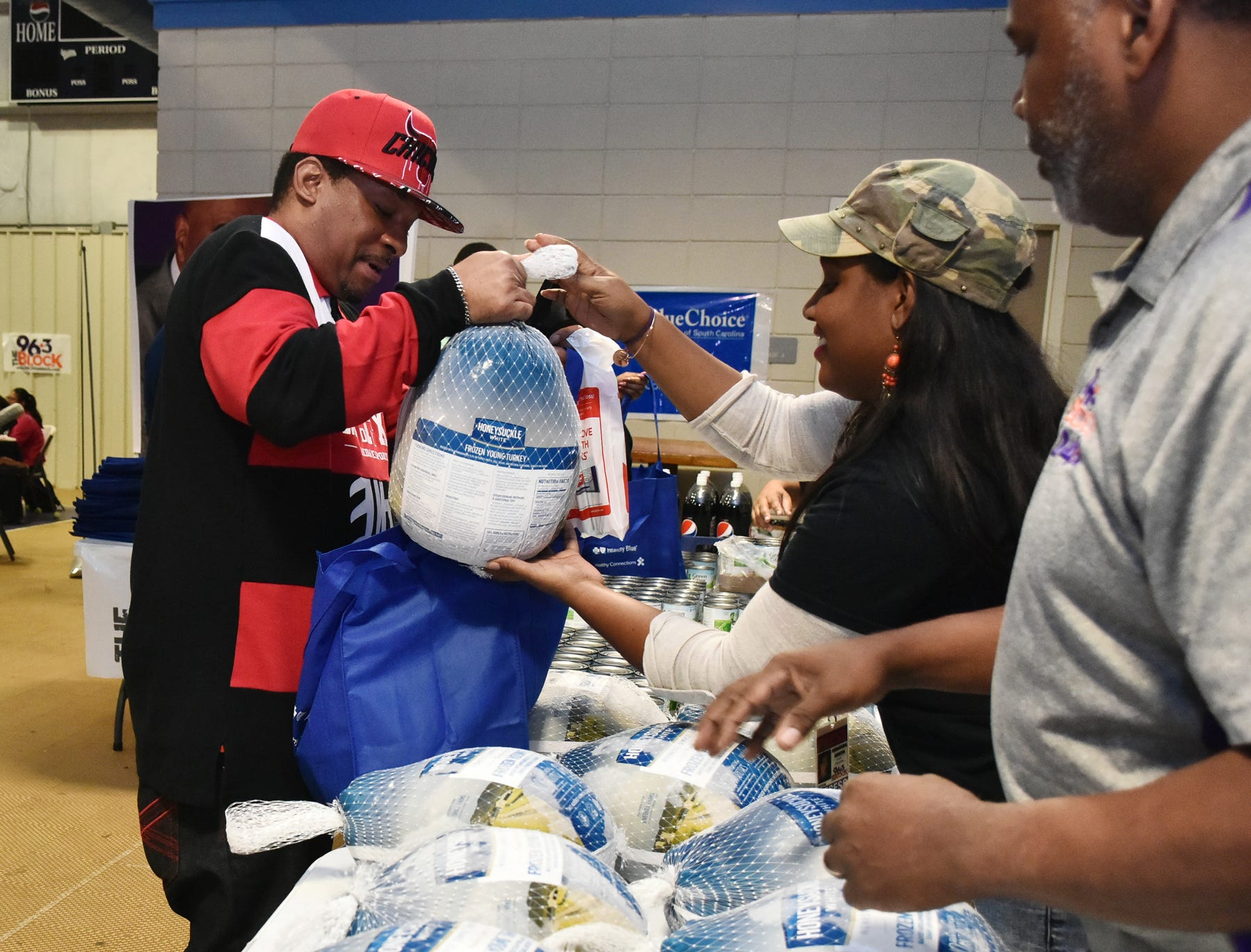 Miranda Asson, an on-air personality at The Block, 96.3 in Greenville, hands out turkeys during The Block presents The Steve Harvey Morning Show Turkey Give at the Freetown Community Center Tuesday evening, November 20, 2018.