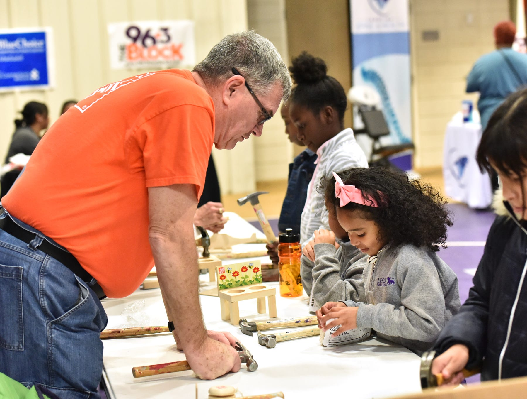 Home Depot employee Ron Catlett helps children with crafts during The Block presents The Steve Harvey Morning Show Turkey Give at the Freetown Community Center Tuesday evening, November 20, 2018.