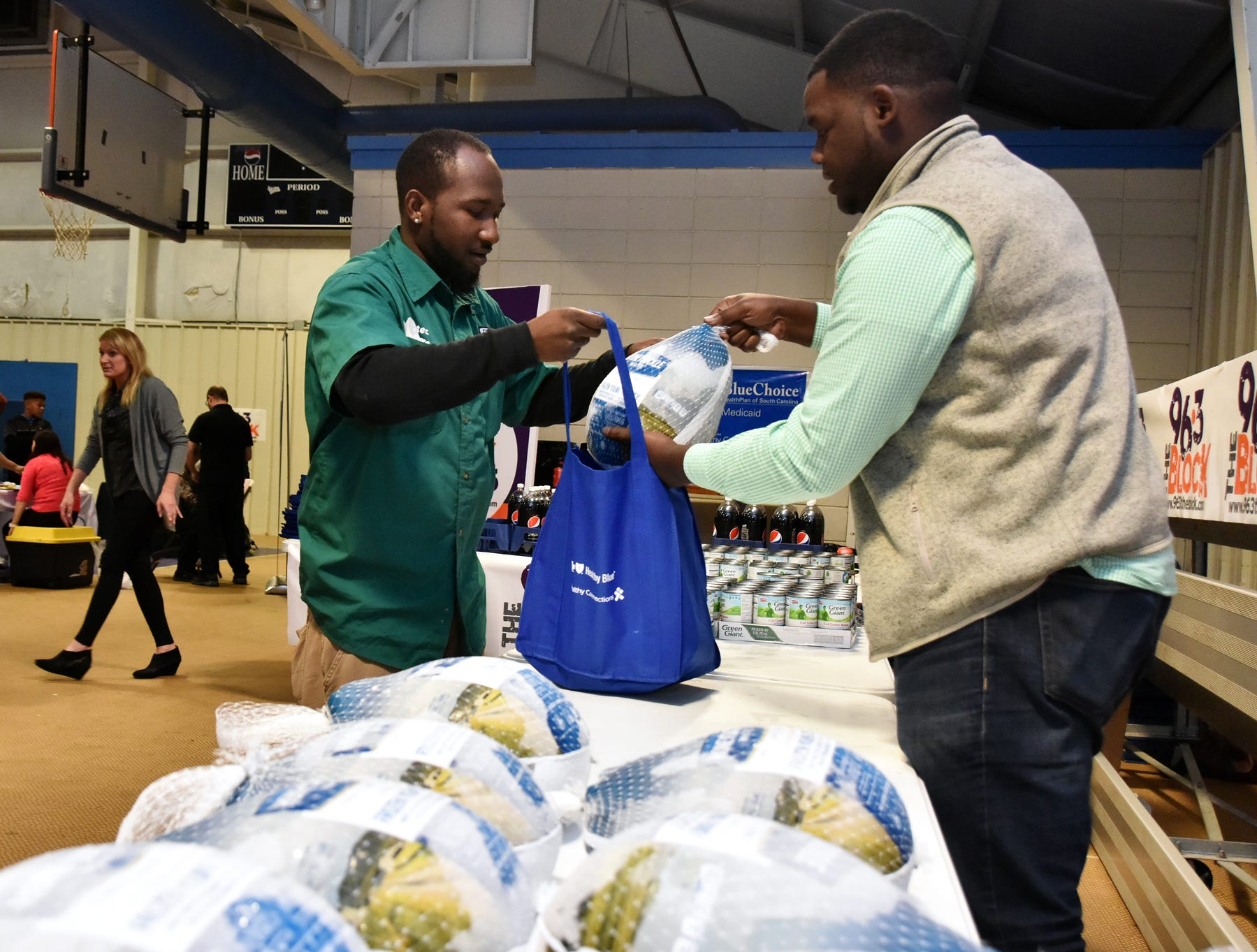 Volunteer Jeremy Robinson hands out turkeys during The Block presents The Steve Harvey Morning Show Turkey Give at the Freetown Community Center Tuesday evening, November 20, 2018.