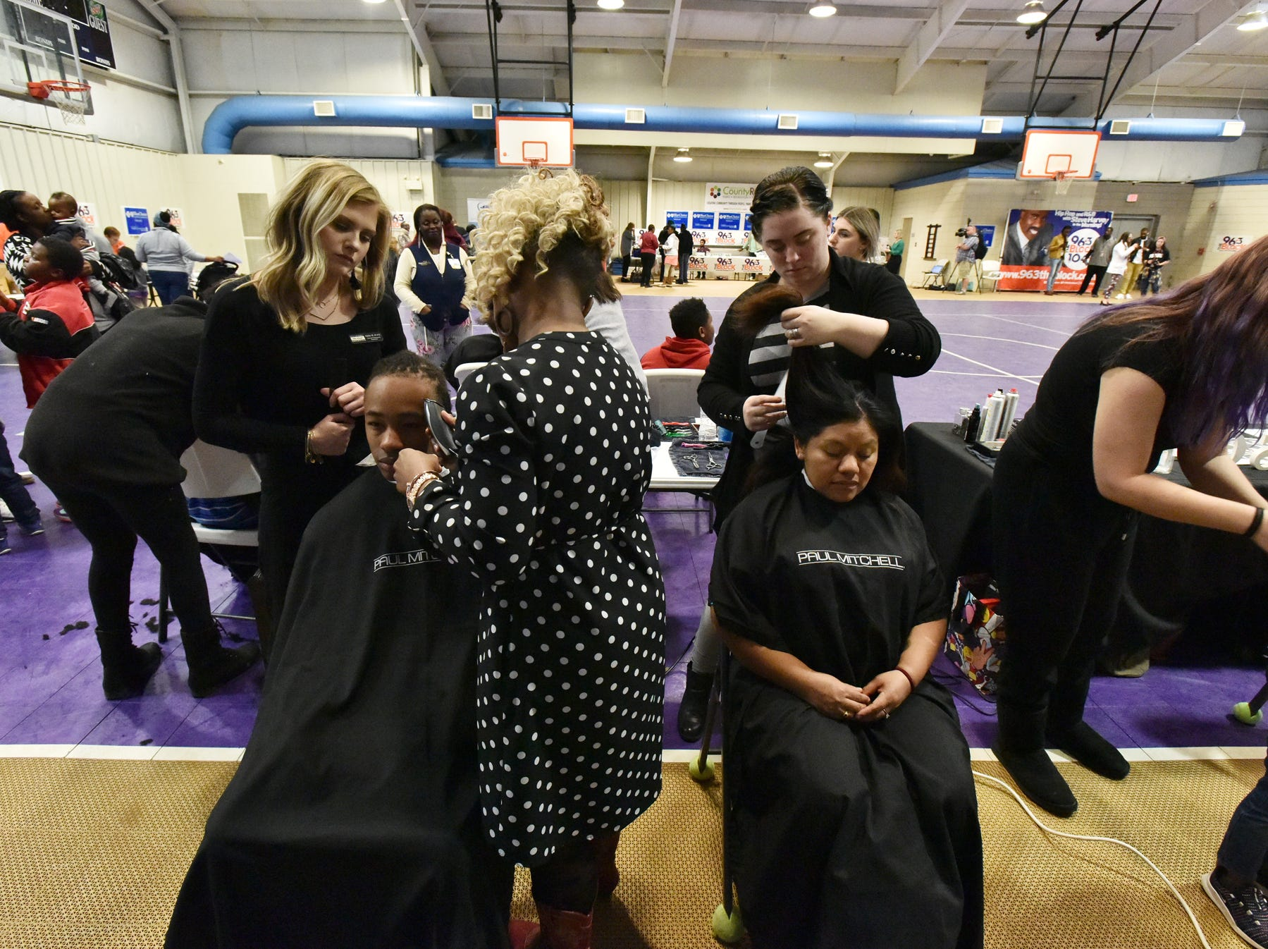 Members of the Paul Mitchell School in Greenville give out haircuts during The Block presents The Steve Harvey Morning Show Turkey Give at the Freetown Community Center Tuesday evening, November 20, 2018.