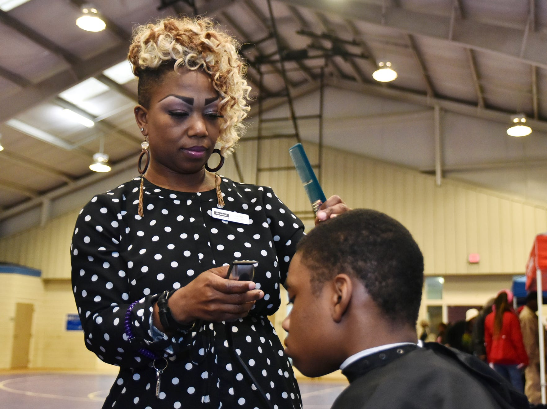 Lecita Porter of the Paul Mitchell School of Greenville gives a haircut to Davion Johnson, 12, during The Block presents The Steve Harvey Morning Show Turkey Give at the Freetown Community Center Tuesday evening, November 20, 2018.