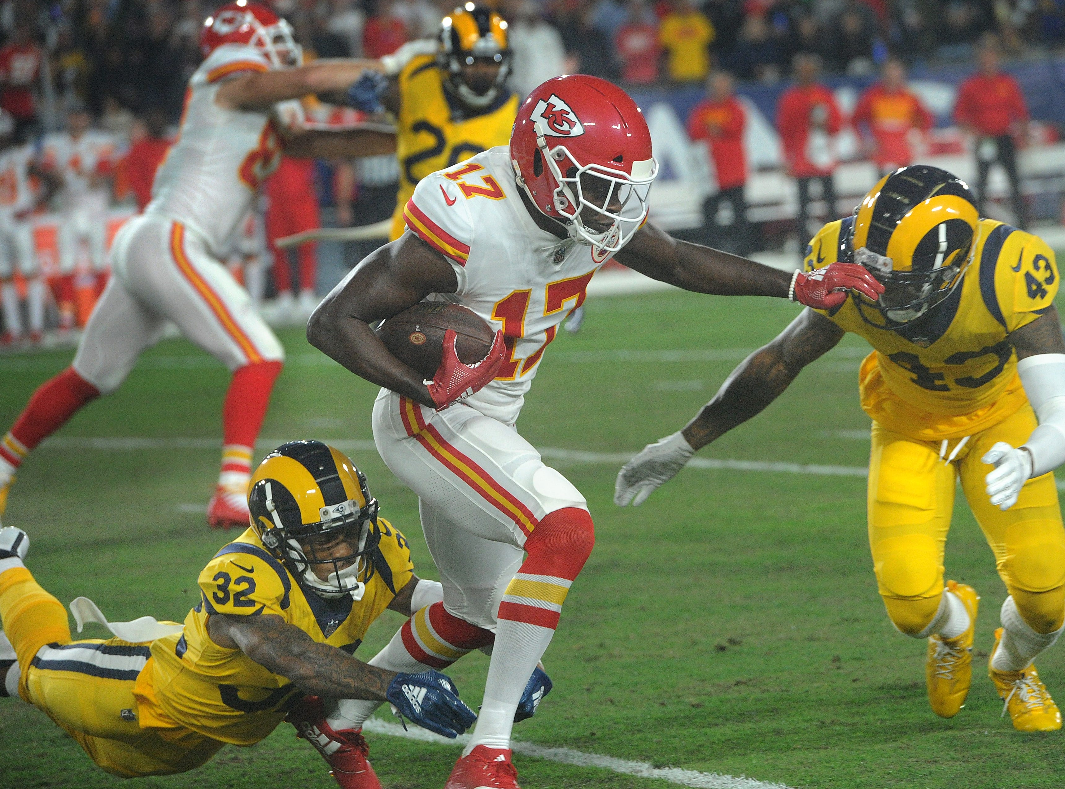 The Chiefs' Chris Conley, center, catches a pass as Troy Hill, left, and John Johnson lll converge for the tackle on Monday against the Rams at the Coliseum.