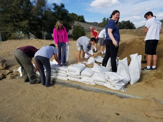 Jennifer Regen looks up from her working filling sandbags Wednesday near Los Angeles County Fire Station No. 89 in Agoura Hills.