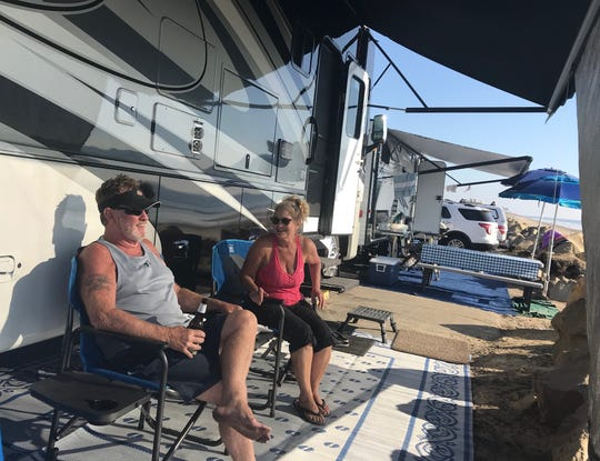 Randy and Nancy Coleman relax beside their motor home on the Rincon Parkway.