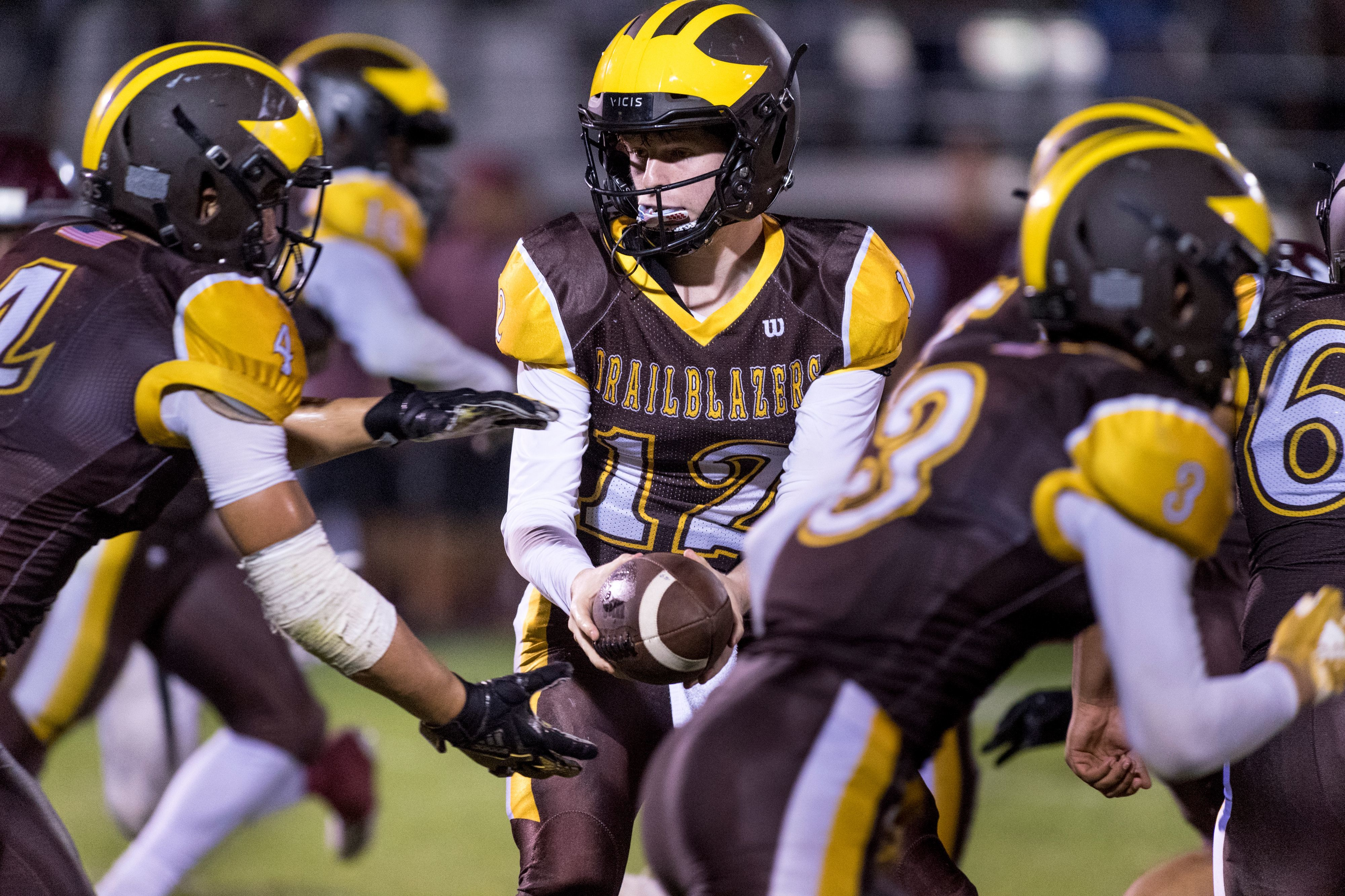 Golden West quarterback Tyson Sandri hands off to Golden West's Lonnie Wessel against Mt. Whitney in a West Yosemite League football game on Friday, September 28, 2018.