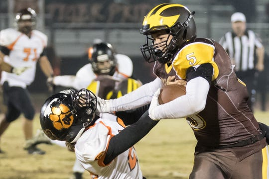 Golden West's Christian Ortiz (5) stiff arms a Wasco defender in a Central Section Division IV high school football semifinal playoff game on Friday, November 16, 2018.