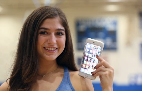 Westlake volleyball player Sydney Roell holds up her phone as she talks about student athletes and social media while in the gym at Westlake High School in Thornwood .