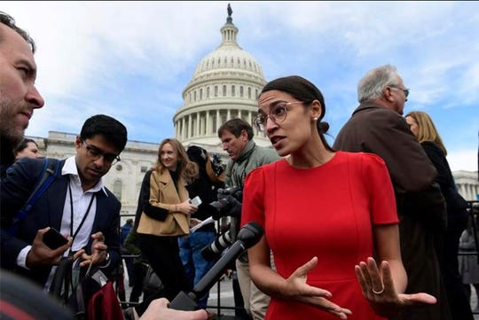 Rep.-elect Alexandria Ocasio-Cortez, D-N.Y., talks with reporters Nov. 14, 2018, following a photo opportunity on Capitol Hill in Washington, with the freshman class. Ocasio-Cortez seems to be everywhere. She's cooked soup, live on Instagram. She's done laundry in public. And she's clapped back at critics of her clothing and a misstatement. The New York Democrat, who at 29 is the youngest woman to be elected to Congress, says she's documenting her journey to Capitol Hill to lift some of the mystery of the place and make it, 'real.'