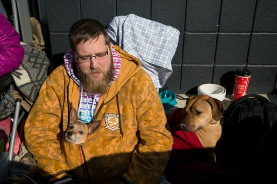 Mike Farrar of Claymont and his dogs Jo jo and Emmit cuddle up with him as they wait in line for Black Friday at the Best Buy store in the Christiana Fashion Center.