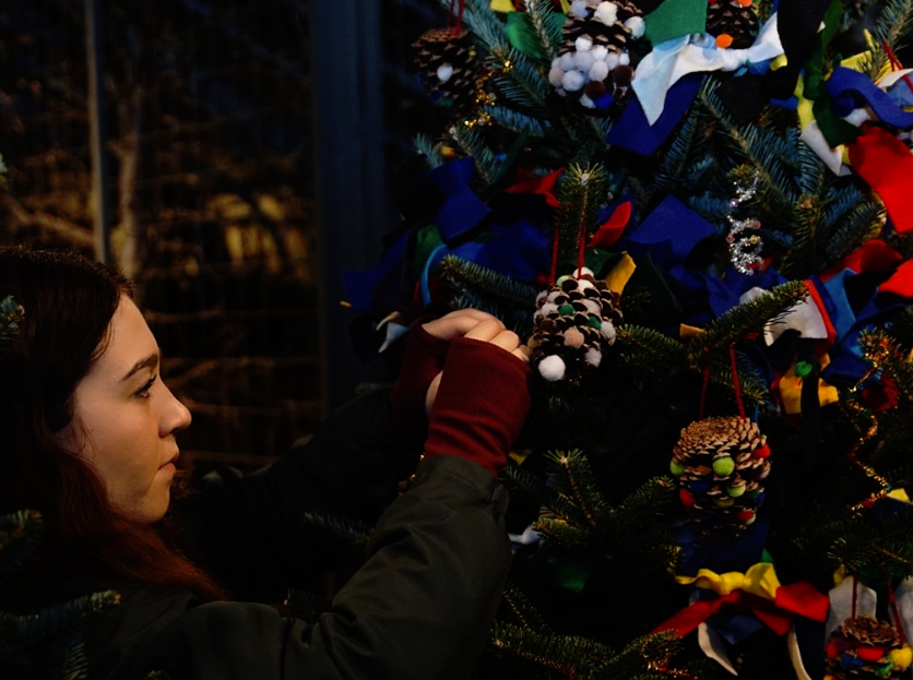 """Education Intern Julie Raiguel hangs ornaments created by MOT Charter School. Every year, Longwood selects students from 13 schools to design and craft hand-made ornaments. This year's theme is the way children imagine a Christmas tree. """"I love to see all the kid's original pieces of artwork,"""" said School & Youth Manager Michelle Cugini, """"no two are the same."""""""
