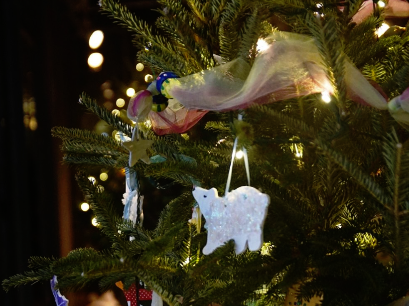 """Oberle Elementary School students chose to decorate their tree with snowflakes, polar bears, and penguins, finding inspiration from a photo of emperor penguins standing under the Aurora Borealis. Penguins hold a special place in their hearts, as their mascot is """"Pete the Penguin."""""""
