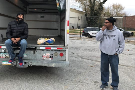 Jaron Johnson (left) and Minster Arthur Bowers helped provide East Side residents with 400 turkeys for the holiday Wednesday afternoon in the Christian Growth Ministries' parking lot.