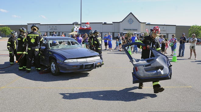 Members of the Wood County Sheriff's Rescue dismantle a car Tuesday during National Night Out in 2013.