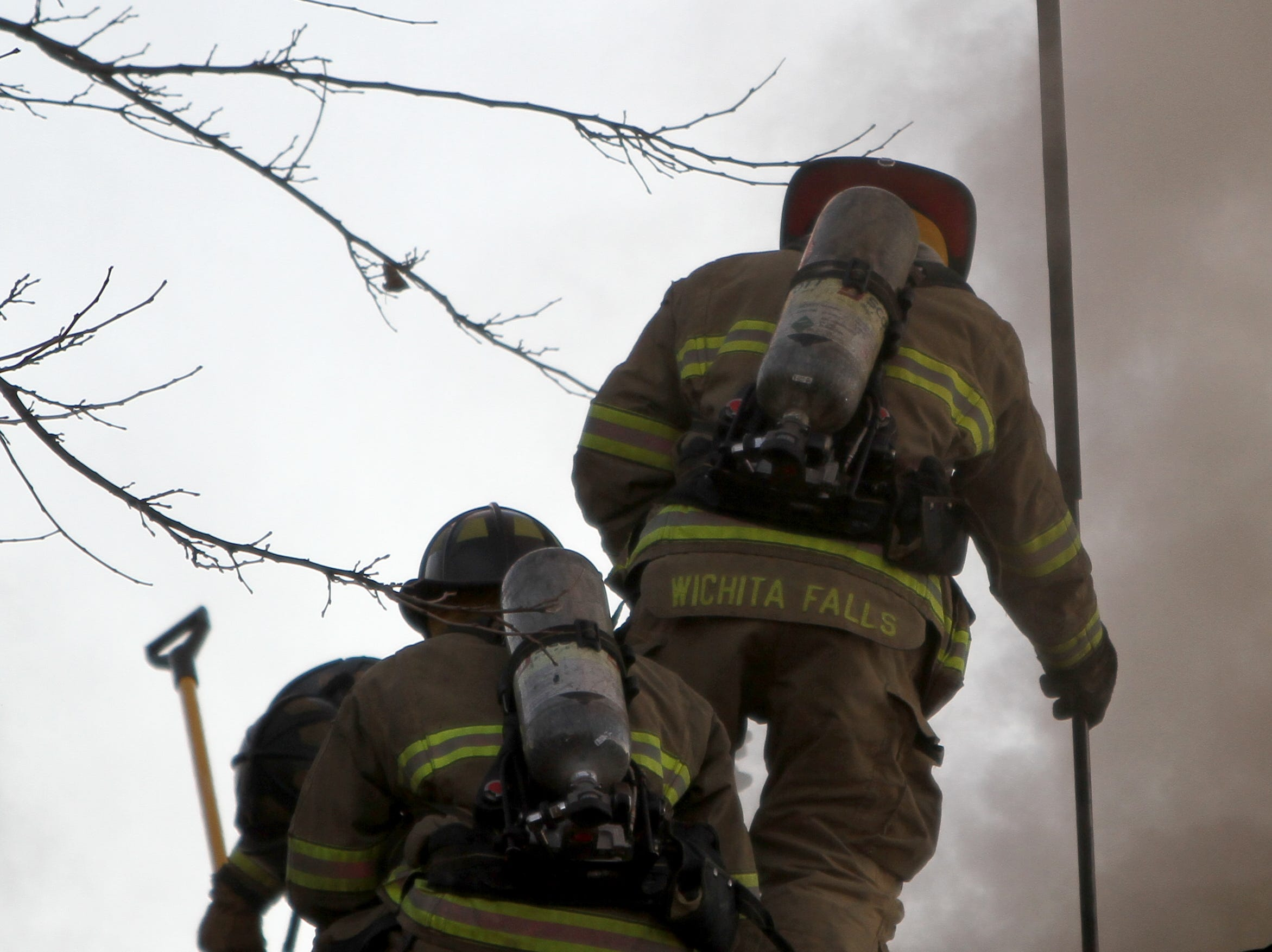 Firefighters work to cut through the roof to put out a fire Tuesday, Nov. 20, 2018, at The Woodlands Apartment Homes on Midwestern Parkway.