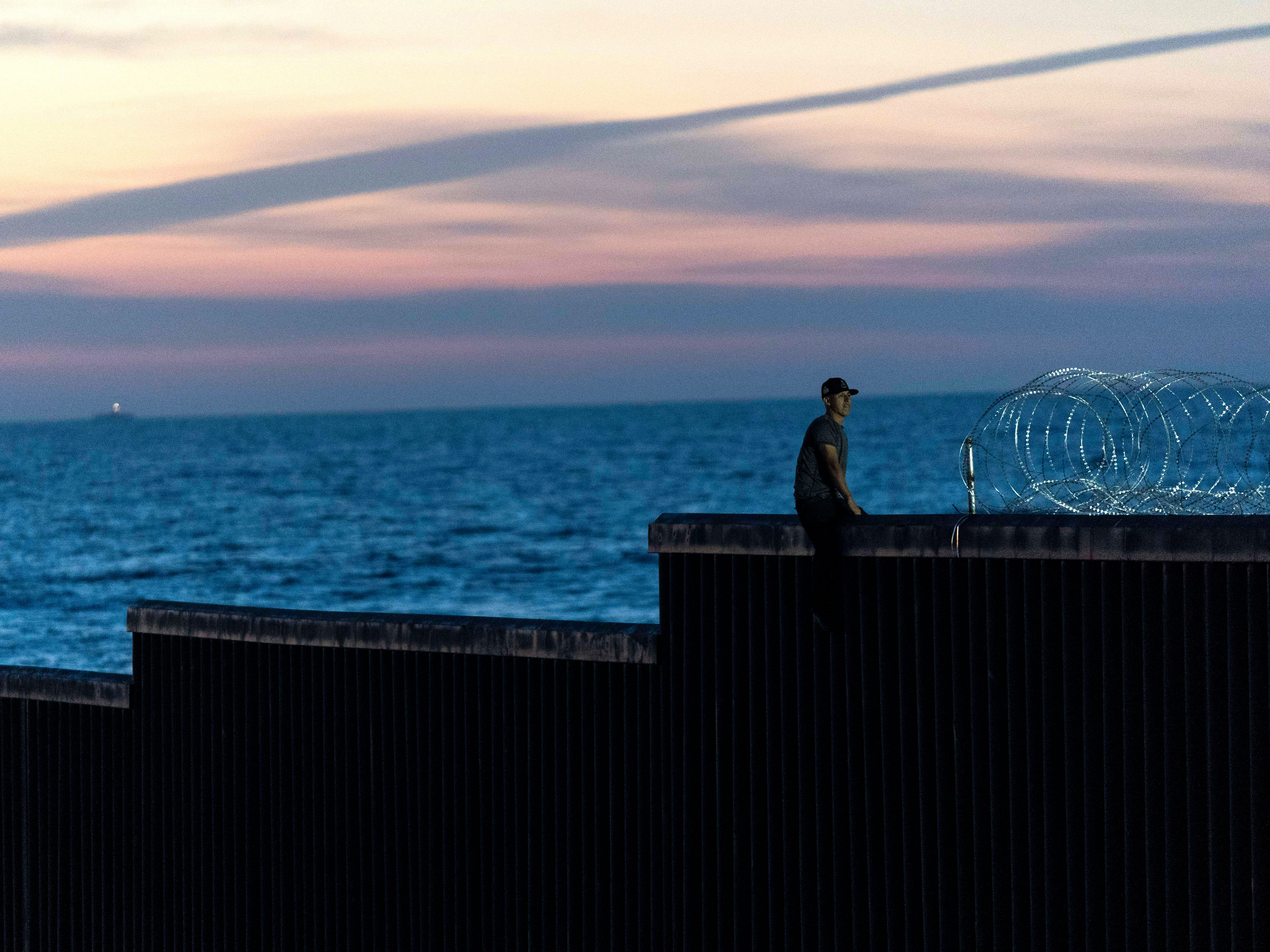 A man tries to climb over the U.S.-Mexico border fence at Playas de Tijuana, Mexico on Nov. 18, 2018.