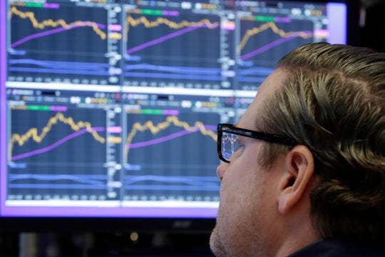Specialist Gregg Maloney works at his post on the floor of the New York Stock Exchange.
