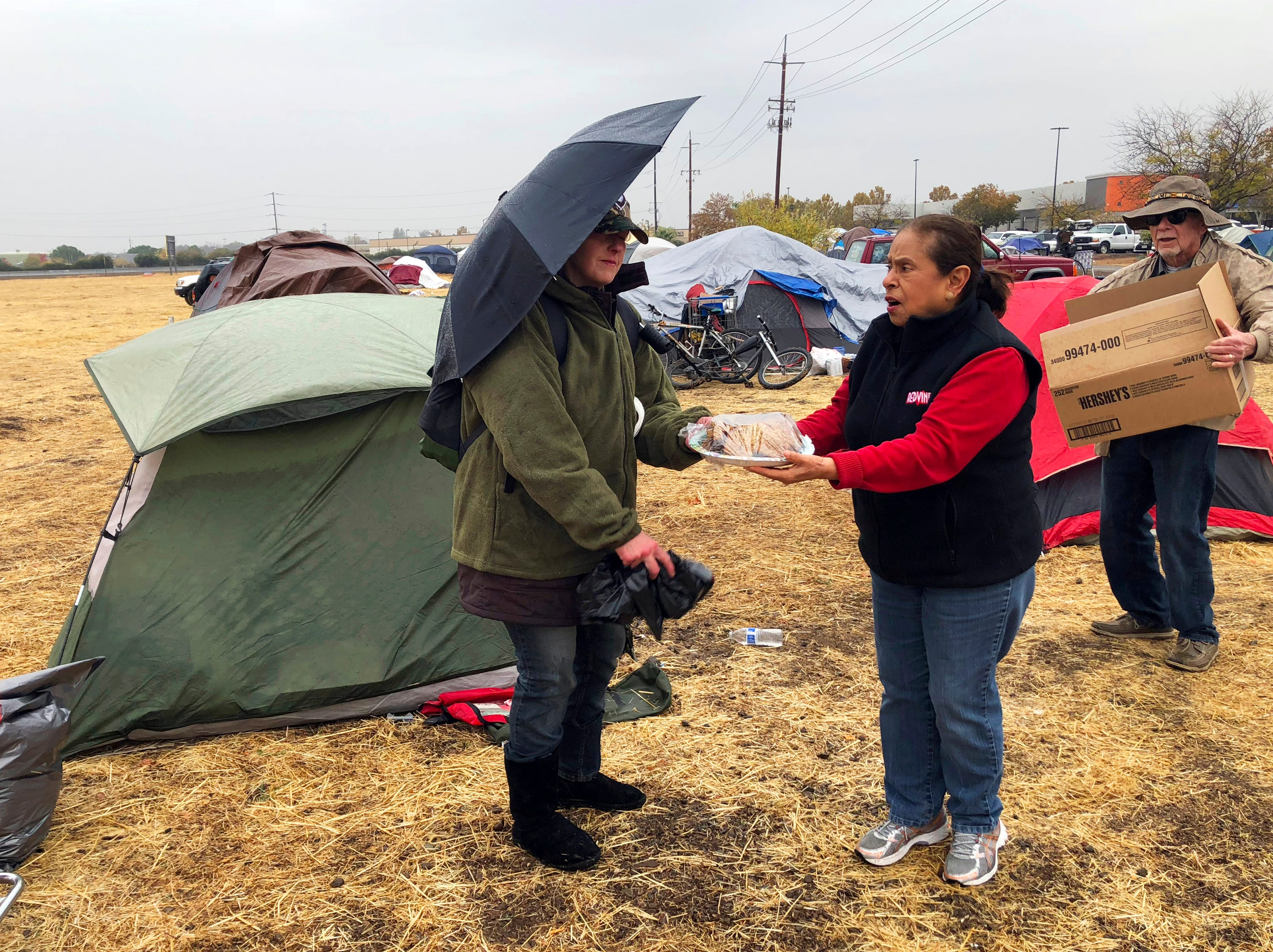 Amy Sheppard accepts banana bread from Margarita and William Bradbury as she packs up items outside her tent in a Walmart parking lot in Chico, Calif., that's been a makeshift campground for people displaced by wildfire, Wednesday morning, Nov. 21, 2018. Sheppard lost her home in Magalia to the Camp fire. She was staying in the tent for four days with her sister and 1-year-old niece. They are moving to a motel because of rain that began Wednesday.