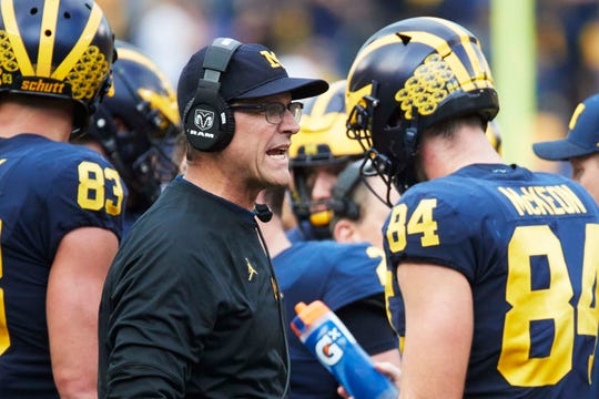 Michigan coach Jim Harbaugh talks to one of his players on the sideline during a game in 2018.