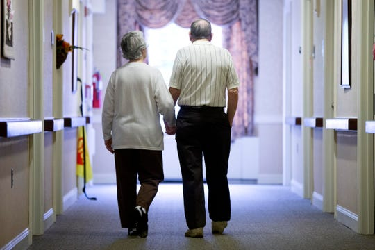 Decima Assise, who has Alzheimer's disease, and Harry Lomping walk the halls at The Easton Home in Easton, Pa.