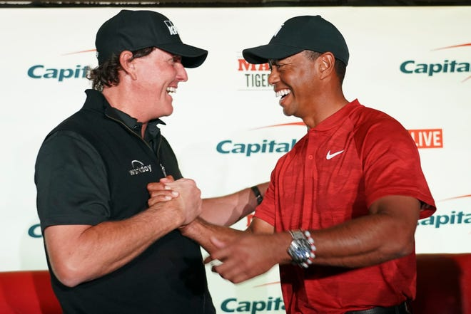 Phil Mickelson and Tiger Woods shake hands during a press conference before The Match: Tiger vs Phil golf match at Shadow Creek Golf Course.