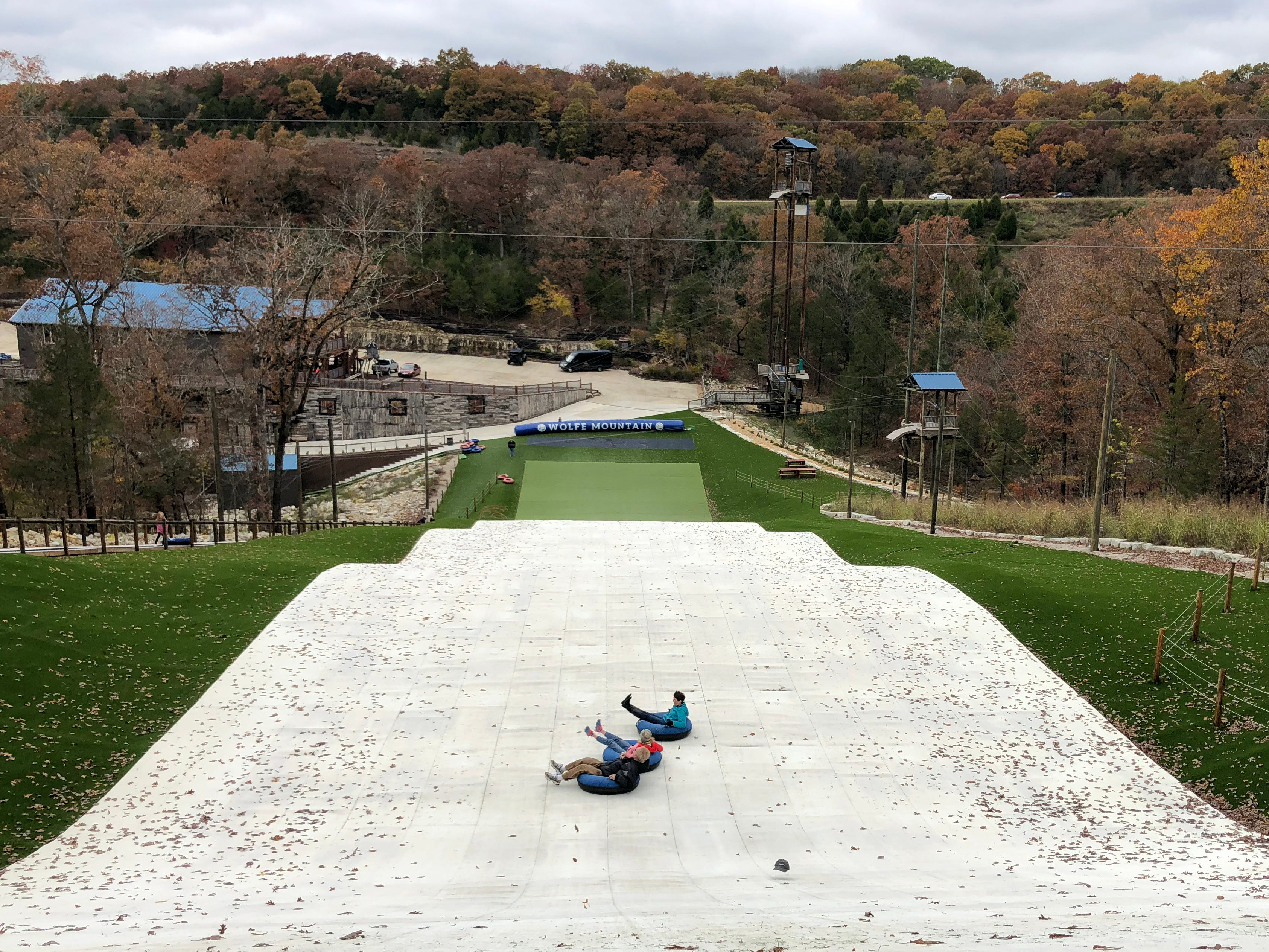 At the Snowflex hill at Wolfe Mountain, visitors pile into tubes and soar down a steep slope covered in a synthetic material that mimics snow.