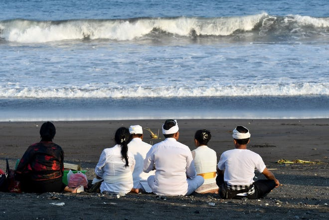 """File picture - this photo taken on October 13, 2018 shows a priest and devotees offering prayers to the deities during the """"Tolak Bala (warding off misfortune) rituals at the Pura Campuhan Windhu Sagara temple on the Padang Galak beach in Denpasar, Bali."""