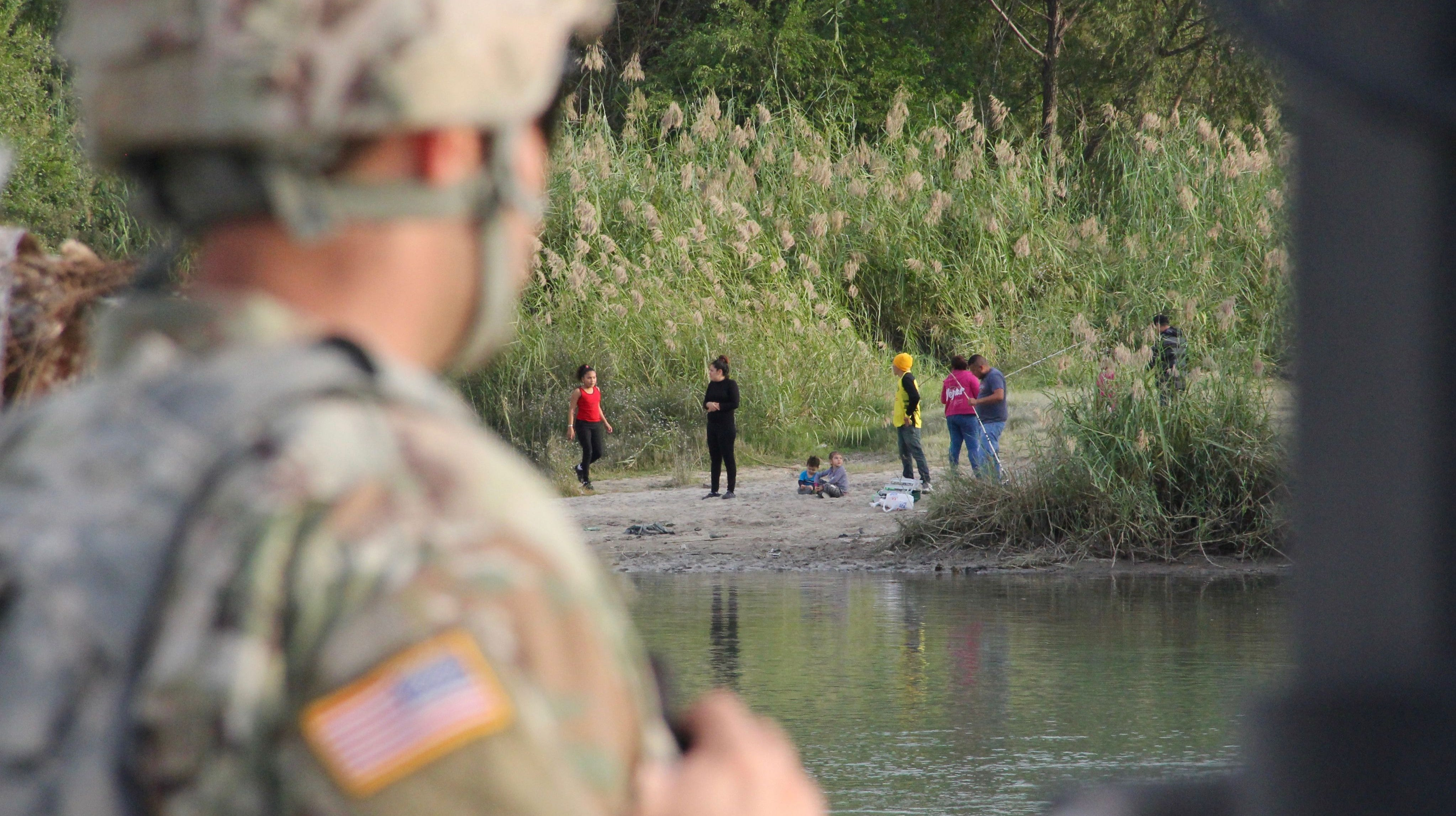 A soldier from the Kentucky-based 19th Engineer Battalion looks across the Rio Grande River from Laredo, Texas, into Nuevo Laredo, Mexico, where a group of people hang out on the river bank on Nov. 17, 2018.