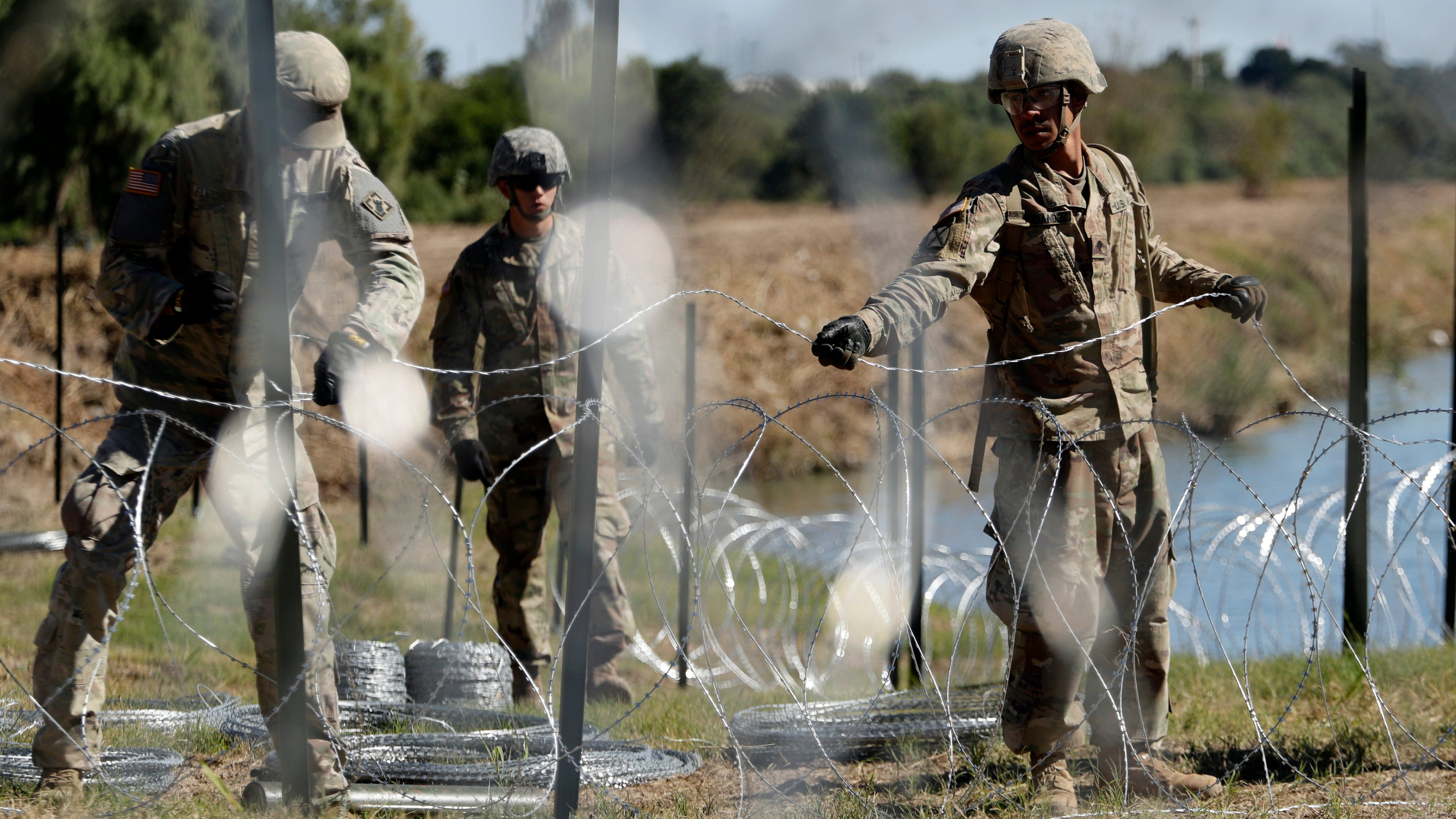 Members of the U.S. military install multiple tiers of concertina wire along the banks of the Rio Grande near the Juarez-Lincoln Bridge at the U.S.-Mexico border in Laredo, Texas.